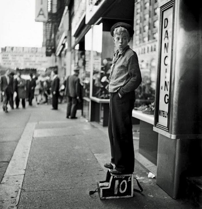 Un ragazzo lustrascarpe in attesa di un cliente