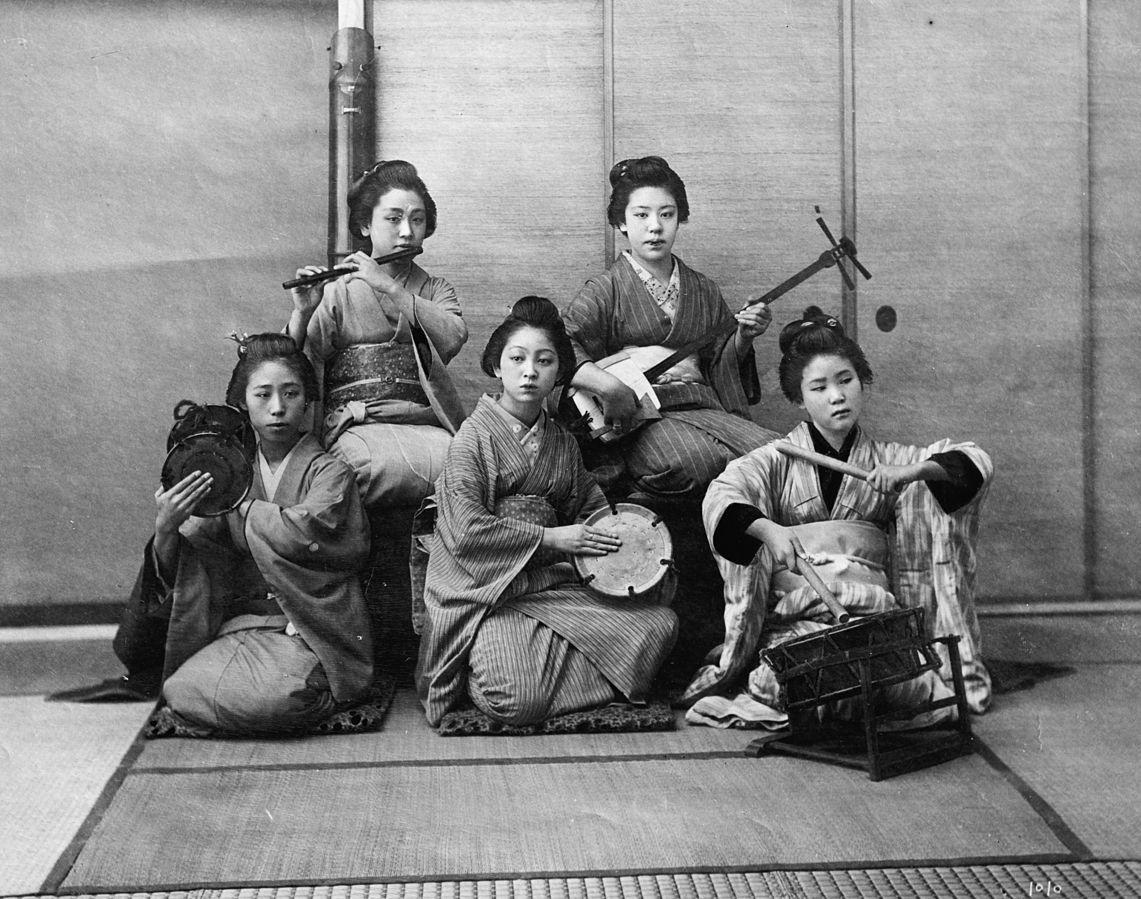 Delle giovani mentre suonano vari strumenti musicali: samisen, fuye, taiko, e tsuzumi.
